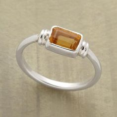 A lone citrine casts a lingering golden light from its sterling bezel. Sterling silver band. Exclusive. Whole sizes 5 to 9.