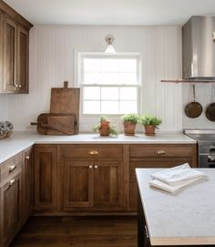 Medium stained cabinetry with white tongue and groove backsplash + brass cup pull hardware + farmhouse shaker kitchen | Lauren Liess