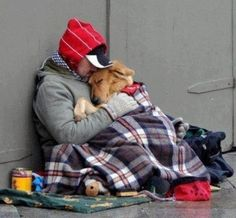 Homeless man snuggles with his dog.
