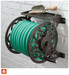 This decorative hose reel has a convenient storage shelf for your gardening tools and hose accessories. Water Hose Holder, Garden Hose Holder, Garden Hose Storage, Best Garden Tools, Steel Hose, Hose Reel, Walled Garden, Home Vegetable Garden, Steel Wall