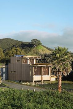 On New Zealand's Great Barrier Island, two architects designed a petite holiday home that takes care of its own water, electricity, and sewage needs.