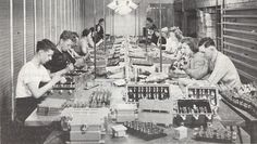 Mostly women and young men assemble Navy electrical control panels.