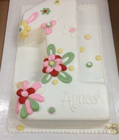 Cake in shape of number one all in white with modern flowers in drastic contrast for a girls first birthday