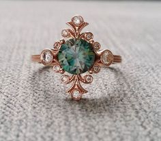 Vintage Inspired Engagement Rings by PenelliBelle ~ The Fountainhead features a 14K rose gold etched antique art nouveau style setting. Set with a .80 ct teal blue green moissanite and 0.30 ct of natural full cut bezel set diamonds #weddingshoes