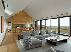 Inside this home, a wall of floor-to-ceiling windows match a door that opens to the balcony. The main floor with a peaked roof, is open plan with the kitchen, dining and living area all in the same room.