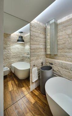 vasque en pierre, revêtement mural en pierre blanche, sol en bois et grand miroir mural