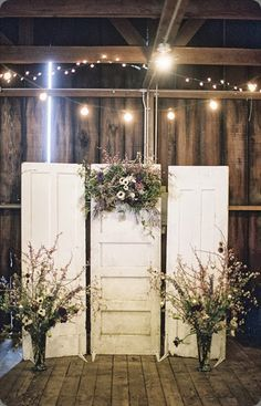 A clever way to use old doors and dried flowers to create a rustic backdrop for a photo booth or even behind a bridal table! Indian wedding decor - Engagement party decor - vintage wedding decor - rustic decor - photo booth backdrop - DIY photo booth ideas - fairy lights #thecrimsonbride