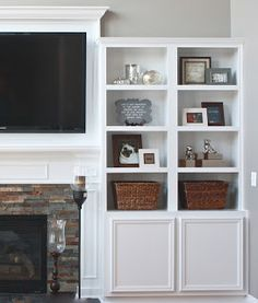 Built in bookcase next to tv, framed tv with larger molding on top of TV.