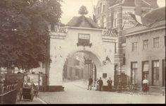 """Oude Vismarkt vanaf de Grote Markt naar het oosten gezien ca. 1921. Feestpoort t.g.v. oranjefeest? Op de poort staat VIVAT ORANJE en jaartal 1526, in de boog """"Doe wel en zie niet om""""."""