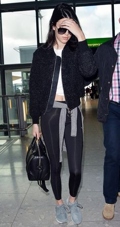 Kendall Jenner is comfy in a crop top, leggings, bomber jacket, Givenchy satchel, and gray sneakers