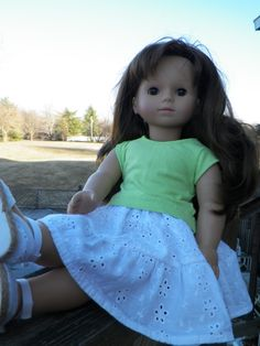 White eyelet layered skirt cut apart and remade into skirt with elastic waist for the doll.  Lime green knit top with little cap sleeves and slight flare just below waist.  Easy on and off with velcro down back.