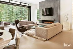 Designer Carol LaCour positioned custom Verellen sofas covered with Romo fabric in the living area, which opens through pocket doors to a spacious outdoor living room. Fibre by Auskin's sheepskin rug complements the fireplace, which is clad in stone tile from Loveless Stone & Tile.