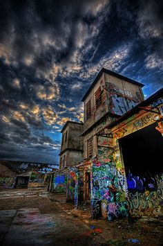 In this beautifully colored shot the light/dark sky seems to twirl around the towers of this abandoned building and the graffiti on the structures' walls comes to life in the half-light.