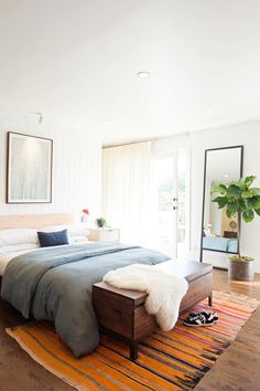 Fresh white walls provide a bright, clean backdrop for this master bedroom. An orange, blue and pink striped rug adds fun color to the space, while a fiddle leaf fig tree adds a natural touch.