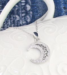 FREE Shipping Both Ways! A filigree design gives an ornate look to this crescent moon necklace edged with sparkling crystals.