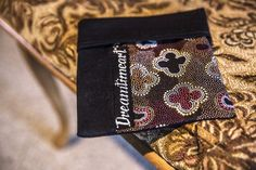 A cosmetic bag made from Aboriginal fabric.