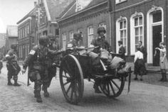 Paratroopers of the 501st move through Niew Straat in Veghel, pushing a farm car for their heavy equipment.