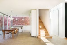 White walls timber stairs and polished concrete with exposed aggregate.