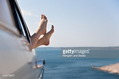 Stock Photo : Woman stretching feet from car by sea