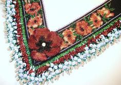 """Beaded Poppy Necklace by Erin Simonetti. """"Field of Poppies Necklace"""".Loomed 25 beads wide in 11/0 Delicas - silver lined and ceylon Delicas, trimmed with lavender ceylon Delicas, matte black Delica bead for background. Petals are a mix of silver lined reds and oranges. The fringe is green glass bugle beads and 8mm lavender acrylic beads that 'glow' in somes."""