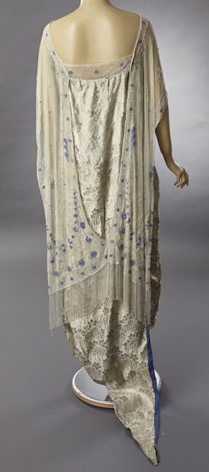 1920s silver lame, silk brocade evening gown covered in silver and blue crystal beads. The dress is a net tabard covered in silver and blue crystal beading. Back
