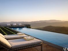 An infinity pool at the garden's north end overlooks the valley. Inset stone pavers turn the lawn into an artful grid, a design by Blasen Landscape Architecture. The Roda chaise longues are from Brindisiamo. Dominick DiTucci -  Keller Williams Realty -  www.dominickditucci.com