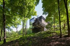 This home is located in a small Berkshires township on a densely wooded, 16-acre property. The site initially afforded no views and little sun penetration, its topography defined by a steep slope, a vertical rock ledge along its east edge, and a creek