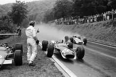 Graham Hill giving the Thumbs up at his teammate Jo Siffert, Lotus, Rouen-Essarts, 1968 Grand Prix. John Surtees (2nd), Honda passing by. Jacky Ickx won the race.