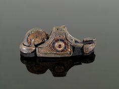Pomo de espada. 'The Staffordshire Hoard'. Siglo VI-VII. Entre los más de setenta pomos de espada éste es especialmente relevante. Anglosajón en estilo, también muestra influencias del arte britón o irlandés. Su disco central con incrustaciones de granates y cristal puede representar una cruz cristiana, pero está roadeado por un motivo en forma de  tres serpientes. Además es el único ejemplar conocido hasta el momento de 'hring-mæl' o 'ring-hilt spatha' que presenta dos anillos en el pomo.
