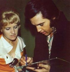 Elvis signing his record for a fan