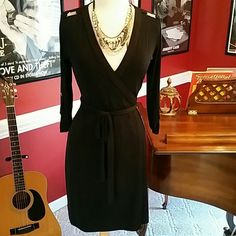 NWT Black Calvin Klein Wrap Dress with Gold Accent I bought this Calvin Klein dress from a boutique.  It's been in my closet, never worn with tags.  It is such a beautiful black dress with edgy gold hardware.  Sleeves can be worn 3/4 with button or down for a long sleeved look.  The material is 95% polyester and 5% spandex. Calvin Klein Dresses Long Sleeve