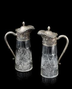 "A pair of silver mounted cut glass claret jugs, Fabergé, Moscow, 1898-1908, of tapering form, glass cut with elaborate pattern of palm leaves, swags, geometric design within rows of palmettes, encased in finely cast and chased mounts in neo-rococo style featuring scrolls, shell motifs, engraved Cyrillic monogram 'ALA' and date ""November 11, 1905'; with long scroll handle chased with ribbon-bound reeded band."