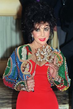 Elizabeth Taylor holds up a diamond mask for photographers at a fine jewelry auction, on April 13, 1992, to benefit the American Foundation for AIDS research (amfAR).