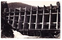A photo postcard c.1911-1913 which shows the construction of the Jordan River Dam, west of Sooke on Vancouver Island. When completed, it was the highest dam in Canada. Photographer unknown.