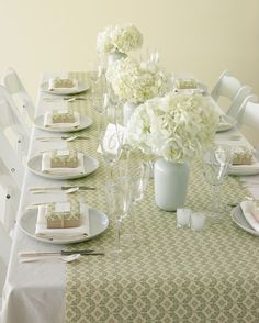 Table arrangements for your wedding that feature hydrangeas.  Simple hydrangea arrangements in white vases are jazzed up by a wrapping-paper table runner.
