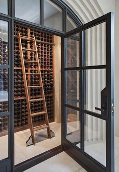 A glass and steel door opens to a wine cellar boasting wooden built in wine racks lined with a wood ladder.