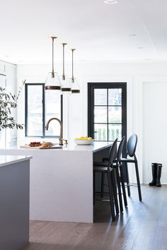 Modern kitchen with an island, upholstered chairs, and bronze and glass pendant lights
