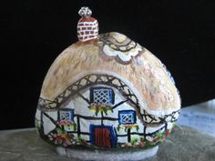 Hand-painted Tudor style English cottage with Thatched roof and flower garden.
