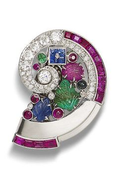A multi-gem set clip brooch, by Mauboussin, circa 1930  The conchoidal brooch set with carved and faceted rubies, emeralds, sapphires and diamonds, diamonds approximately 1.50 carats total, length 4.0cm