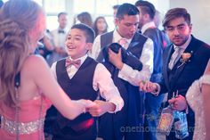 Wedding guest with bottles of tequila dances at Rhinefield House Wedding. .Photography by one thousand words wedding photographers