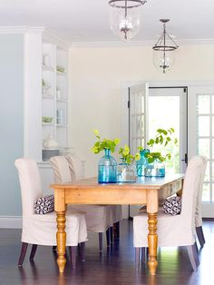 A dream dining room with chairs comfortable enough for lingering over dinner. Pretty, clean and simple. I love the light fixtures (and the turquoise vases!)!