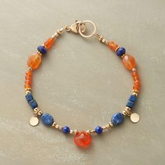 "CIRCLE OF STONES BRACELET -- Bright orange carnelian and deep blue lapis in different shapes and sizes, accompanied by 14kt goldfill beads and dangling disk charms. Lobster clasp. Exclusive. Handcrafted in USA. Approx. 7-1/2""L."