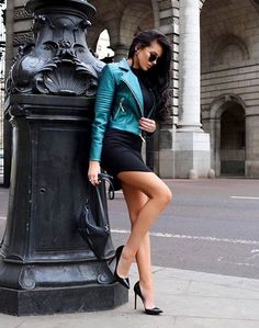 Leggy European honey in an asymmetrical dress and spiffy stilettos carefully propping herself against a statue