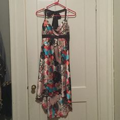 Beautiful dress Beautiful brown and tan halter dress with blue, red and pink floral design. Ties at the neck and ties around the bust. Shorter in the front- measures 25 inches from bust line and 35 inches from bust line to length in the back. It's a perfect summer dress! Iz Byer Dresses High Low