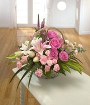 Eloquence. A classic basket arrangement with pink Lilies & Roses.