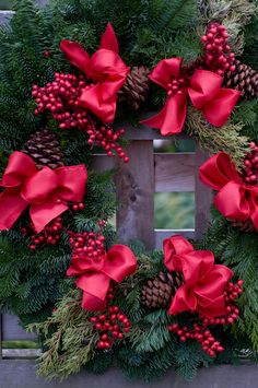 Christmas wreath of fresh mixed greens including fir and spruce with cones and red bows.