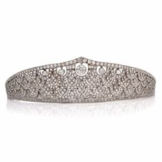 This antique diamond tiara of captivating design and immaculate craftsmanship is handcrafted in platinum and weighs approx. 75.00 grams. This alluring 'Napoleonic' hair ornament is designed as an enchanting assemblage of graduated crescent-shaped profiles, featuring 5 trembling European cut diamonds ranging in weight from 1.55ct to 0.30ct, weighing in total approx. 3.05ct, graded H-I color, VS-SI clarity and enriched with over 715 European cut diamonds weighing cumulatively approx. 17.87ct…