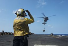 SOUTH CHINA SEA (April 13, 2017) Aviation Boatswain™s Mate (Handling) 3rd Class Victor Romero, from San Diego, signals for an MH-60S Seahawk, assigned to the Blackjacks of Helicopter Sea Combat Squadron (HSC) 21, to deliver pallets of supplies to the flight deck of the amphibious assault ship USS Makin Island (LHD 8) during a vertical replenishment. Makin Island, the flagship for the Makin Island Amphibious Ready Group, with the embarked 11th Marine Expeditionary Unit.