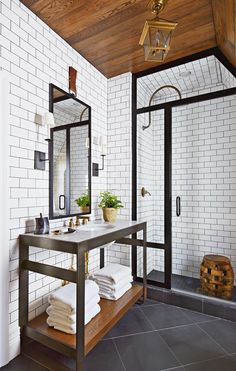 Classic subway tiles combine with antique-inspired fixtures and black metal accents to give this shower an industrial look. Black grout lines give the tiled walls a modern punch that pairs nicely with the shower's black-framed glass door. #bathroomdesign #bathroomideas #bathroomremodel #walkinshowerideas #showertileideas #bhg Dream Bathrooms, Beautiful Bathrooms, Master Bathrooms, Subway Tile Showers, Subway Tiles, Bathroom Renos, Bathroom Ideas, Shower Ideas, Bathroom Designs