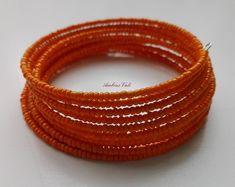 Narancssárga kásagyöngyből fűzött memóriadrótos karkötő.